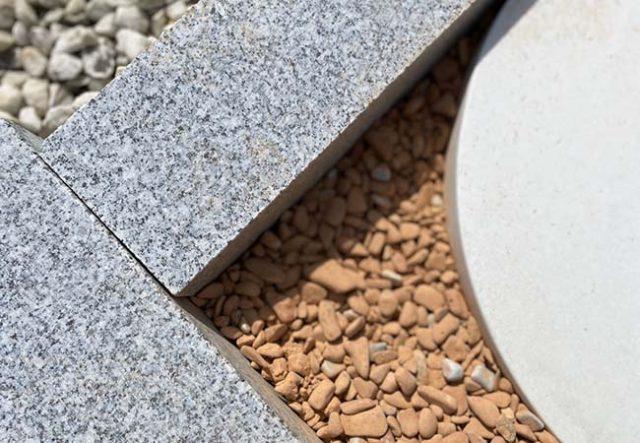 Granit-Bordsteine mit weißem Kies und Schamotte