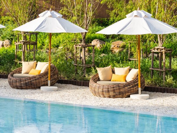 Umbrella and deck chair around outdoor swimming pool in hotel resort with sea ocean beach and coconut palm tree